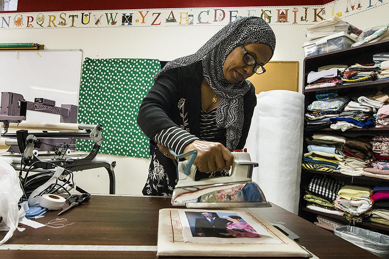 A refugee from Ethiopia named Birtukan (KCUR is withholding her full name due to safety concerns) prepares to set color transfer into the fabric of a wedding photograph for a quilt that will tell of her journey to America.