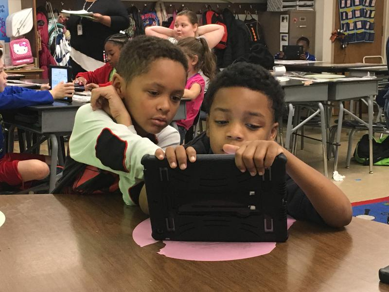 Dominic Young Jr., right, plays an educational game on an iPad with his best friend from second grade, Isaiah Rogers.