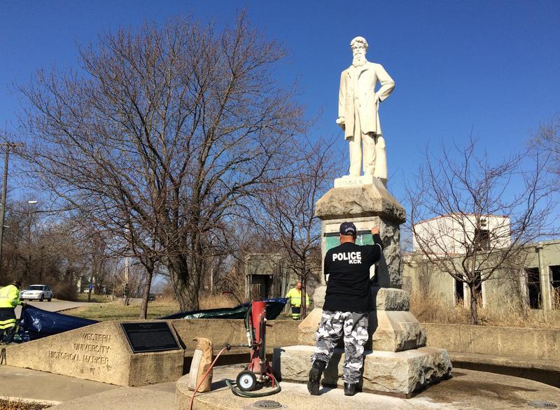 Kansas City, Kansas, police officer Dennis Vallejo prepares to paint over the vandalism on the Quindaro neighborhood's John Brown statue.