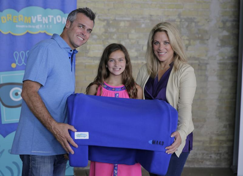 Julia Luetje (middle) holding her invention The Storm Sleeper alongside her parents at a Frito-Lay Dreamvention event.
