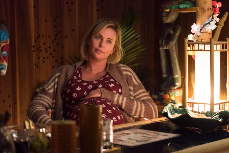 Charlize Theron sits with a pregnant belly.