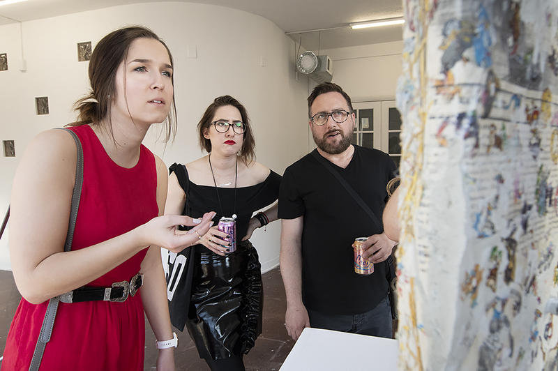 Gallery visitor Melanie Murray (left) talks through her feelings with Melaney Ann Mitchell and Blair Schulman, aka the Guerrilla Docents, at Front/Space in the Crossroads during May's First Friday.