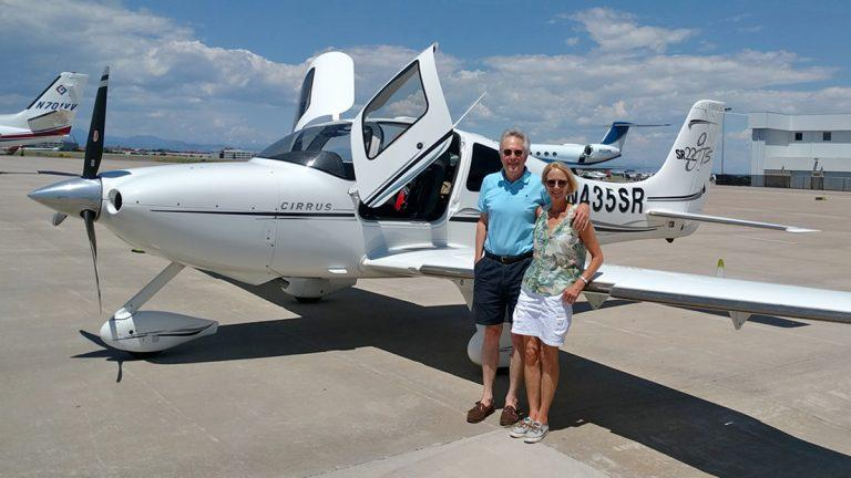 Two people stand in front of a small white prop plane. The background is a blue sky.