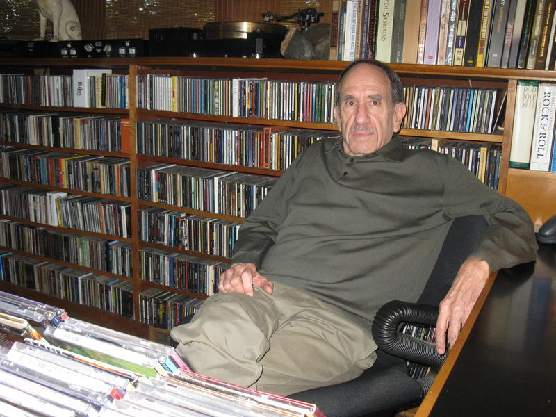 Bill Shapiro sits in a chair, surrounded by CDs, books, and audio equipment.