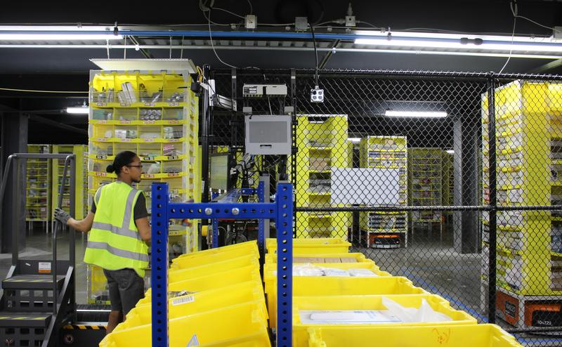 Humans and robots work together at Amazon's new fulfillment center in Kansas City, Kansas. The small, orange robots, shown underneath yellow stacks, scuttle along the floor to retrieve products for employees to package.