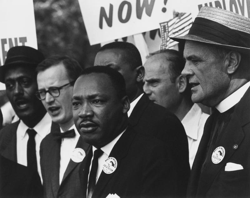 Black and white image of Dr. Martin Luther King Jr. surrounded by people.