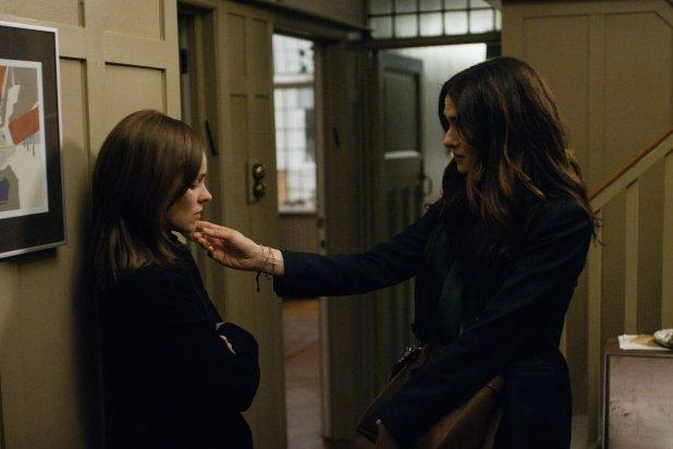 Two women stand in a hallway. One woman touches the face of the other woman.