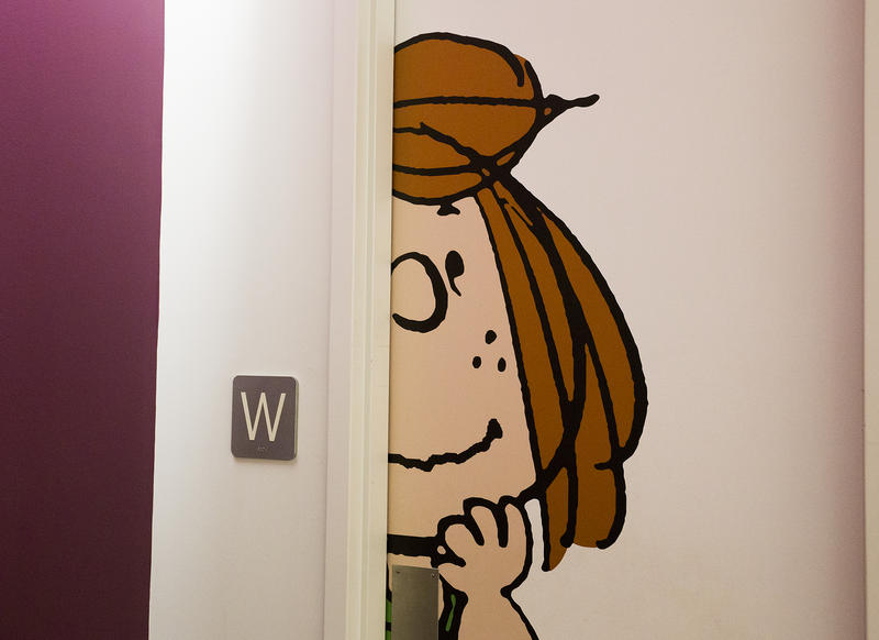 Peppermint Patty, a character from Charles Schultz's 'Peanuts' comic strip, marks the door to the women's restroom at the Andrews McMeel Universal office in downtown Kansas City.