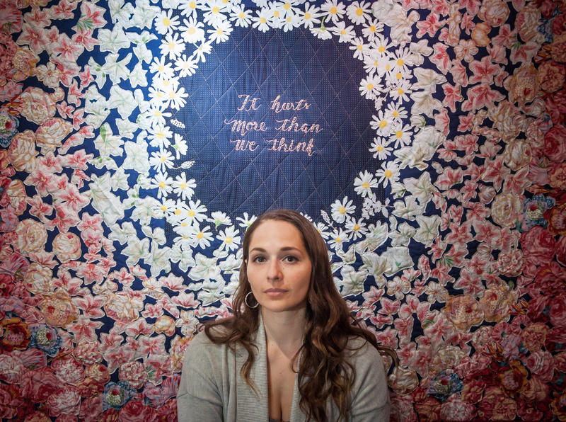 "Artist Jessica Wohl with her quilt titled ""It Hurts More Than We Think"""