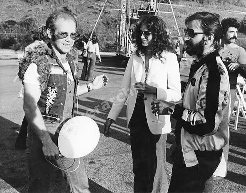 Elton John (left) talks with Ringo Starr (right) and Starr's girlfriend, Nancy Lee Andrews (center) at the Elton John Carnival in Universal City, California, in 1974.