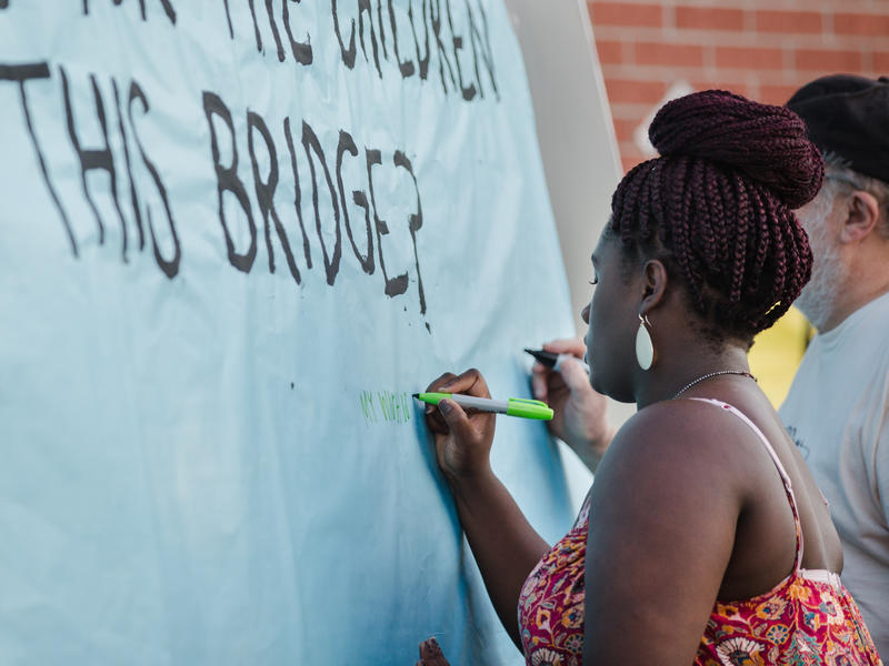 "Khyneesha Edwards signs a banner that says ""What is your hope for the children who cross this bridge?""  Edwards attended Operation Breakthrough as a kid, and although she now lives in Lee's Summit, she's still active in the community."
