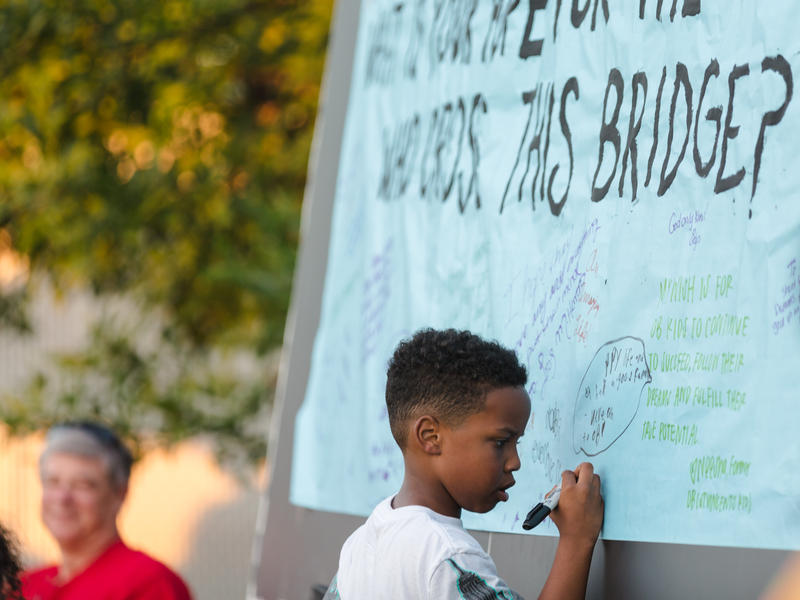 "Kaden Isenhower (7) writes on a banner that says ""What is your hope for the children who cross this bridge?"" Isenhower attends Operation Breakthrough with his two siblings and will be among the many children who benefit from the bridge and addional space."