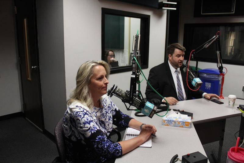 A blonde woman and a man with dark hair sit at a desk behind microphones.