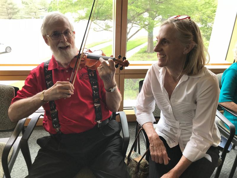 Dennis McCurdy tried out a tiny violin during the May meeting of Memory Cafe, which featured a special guest from the Kansas City Symphony. Deb Campbell, co-founder of the group's local chapter, looked on.