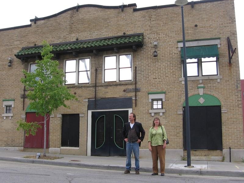 "Actor Chris Coulson and set designer Susan Emshwiller stand outside the Eblon Theater; the facade was used during the filming of ""Kansas City."""