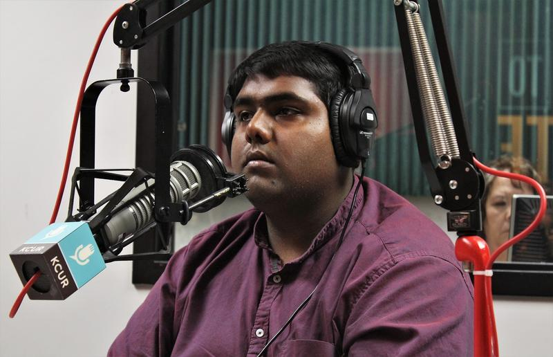 UMKC student Ravi Anand Naidu wearing headphones and seated in front of a microphone at KCUR studios.