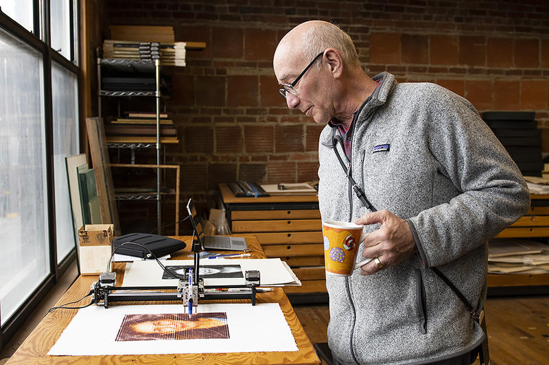 Artist Mike Lyon watches over one of his small drawing machines. Lyon creates large-scale portraits using computer numerical control (CNC) machines to automate the drawing process.