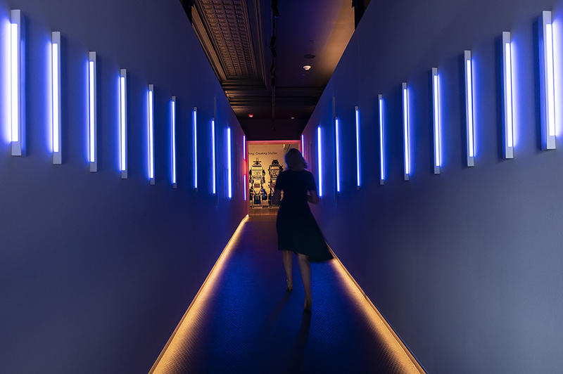 A woman walks through a neon-lit hallway at the entrance of 21c Museum Hotels, the newly redeveloped Savoy Hotel and Grill.