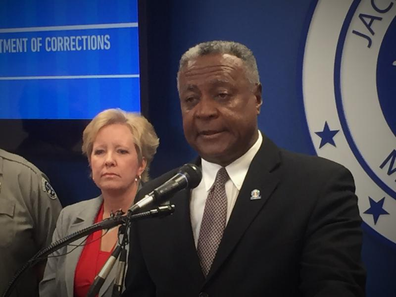 Jackson County Executive Frank White stands at a podium with the Jackson County seal on the wall behind him and to the right and an unidentified woman to the left.