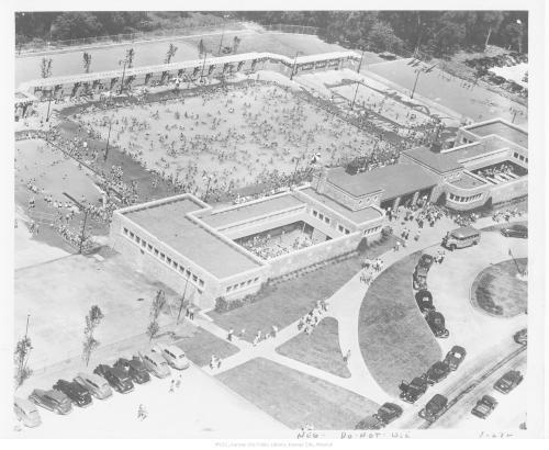 A black and white aerial photo from 1945. It shows a swimming pool filled with people and a parking lot filled with cars.