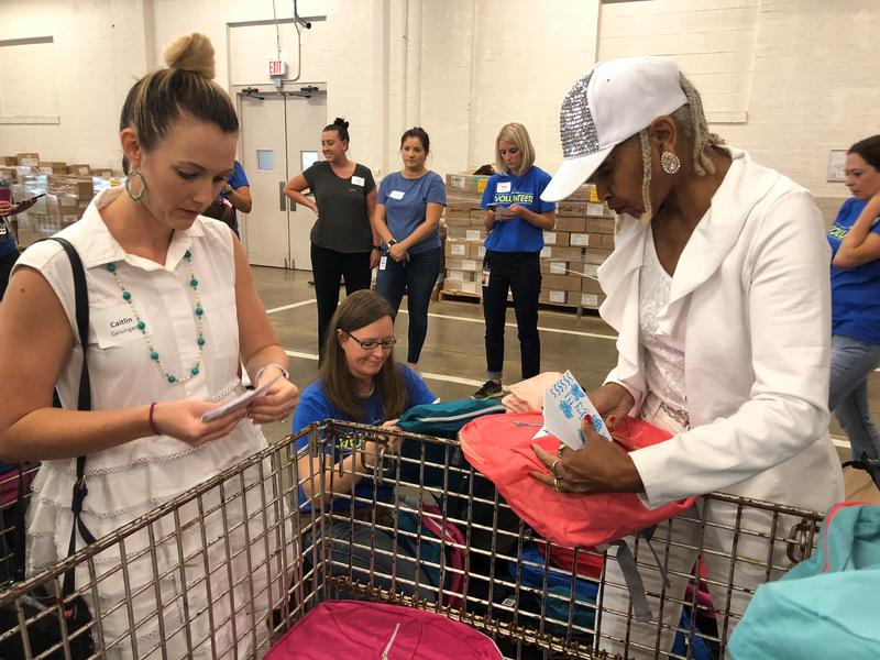 Volunteers stuff backpacks with school supplies ahead of Summerfest, which Kansas City Public Schools holds every year to make sure students are ready to return to class.