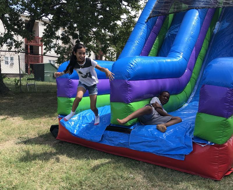 Two Kansas City Public Schools students race down the bounce house slide at Summerfest, the district's back-to-school fair.