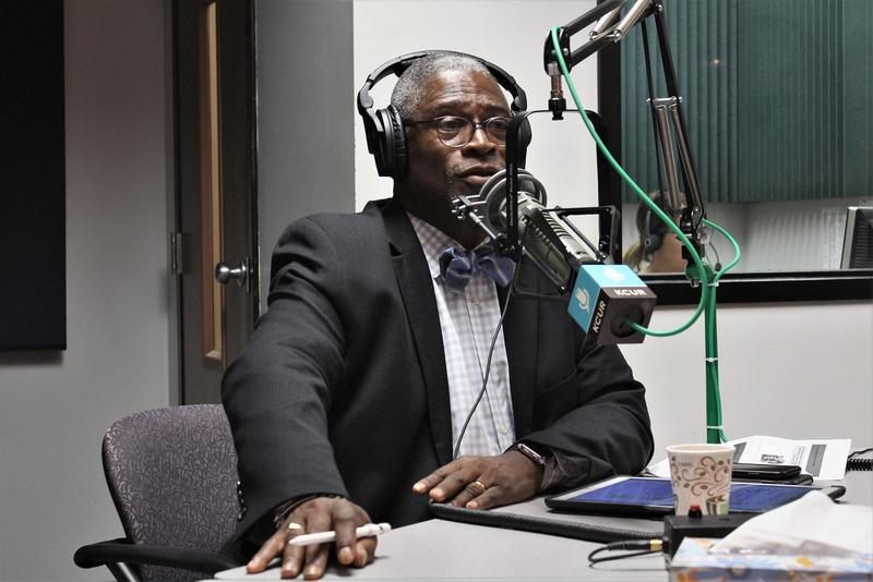 Kansas City Mayor Sly James sits behind a microphone. He is wearing headphones.