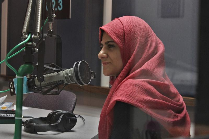 Daniah Hammoude wearing a red hijab sits in front of a microphone in the KCUR studio.