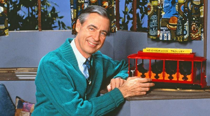 Fred Rogers wearing his trademark sweater sitting next to a toy trolley car on the set of Mr. Rogers' Neighborhood.