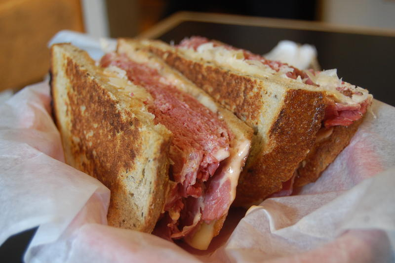 A Reuben sandwich wrapped in white wax paper.