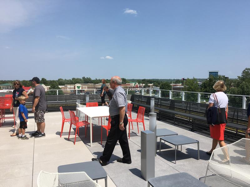 The outdoor deck on the second floor is outfitted with benches, tables and chairs.