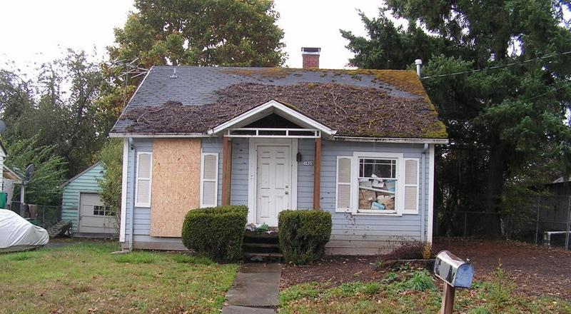 A one story house with a boarded up window on the left, the window on the right blocked on the interior with boxes and junk, and debris on the roof.