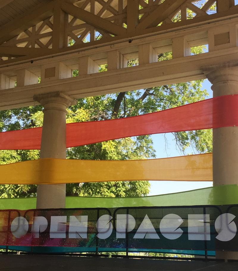 "Grecian-style columns wrapped in colorful banners. A sign that reads ""Open Spaces"" hangs below."
