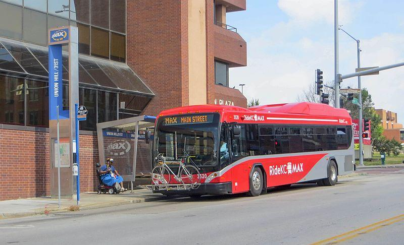 A red and grey commuter bus at a MAX line stop in Kansas City, Missouri.