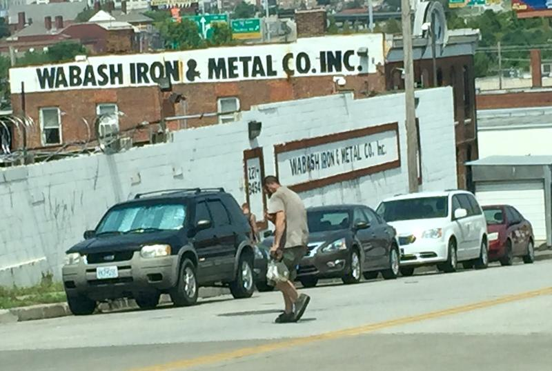 An unidentified man carries copper pipe in a bag to Wabash Iron and Metal near 19th and Troost. The owners of Wabash argued against a proposed ordinance that would impose tougher regulations on scrap metal businesses in Kansas City.