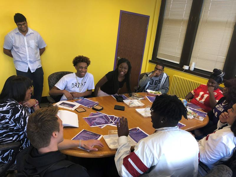 Student advisors to DeLaSalle Principal Elizabeth Sanders laugh during a lunch meeting.