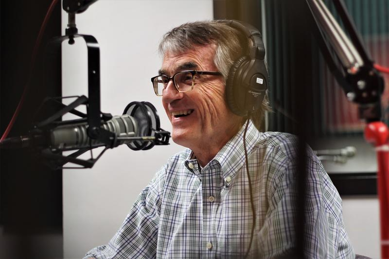A man wearing glasses and a plaid shirt smiles while seated behind a microphone for a radio interview.