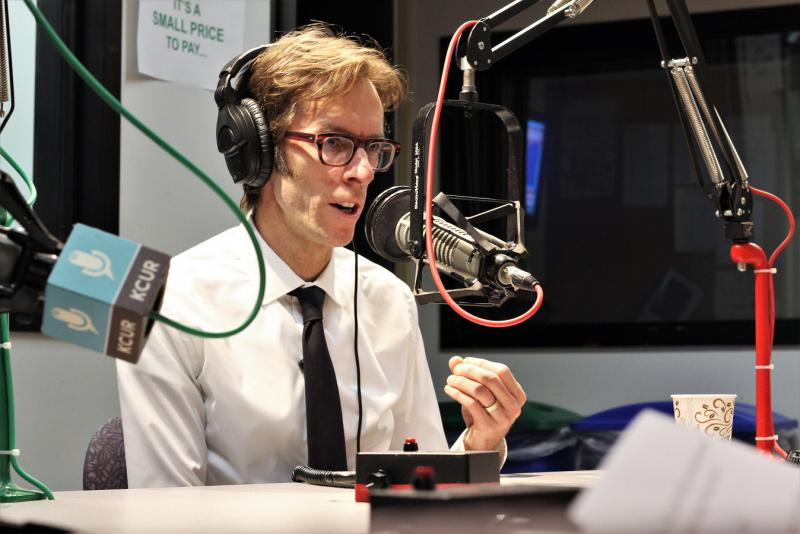 Keith O'Brien, white male in shirt and tie wearing headphones and seated in front of a microphone in the KCUR studio.