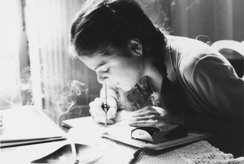 Black and white photo of Gilda Radner writing in a notebook.