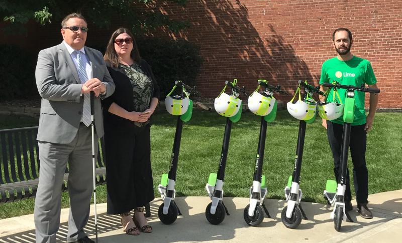 KCATA President Robbie Makinen, Sarah Frost of the Kansas City Regional Transit Alliance and Lime's Sam Sadle pose with five of Lime's electric scooters during the company's Kansas City rollout of its electric scooters in September.