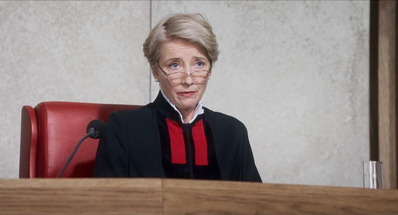 A judge sits at her desk hearing a trial.