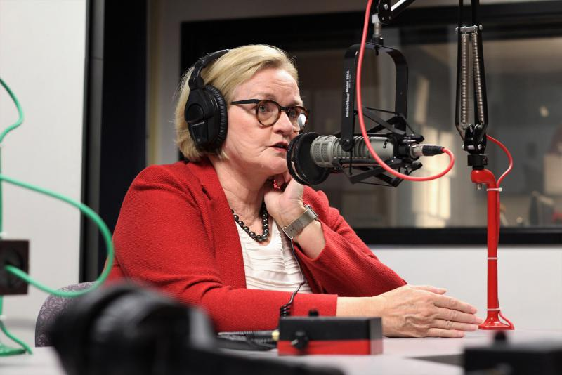 A women wearing glasses and a red sport coat witha white blouse behind at a microphone.