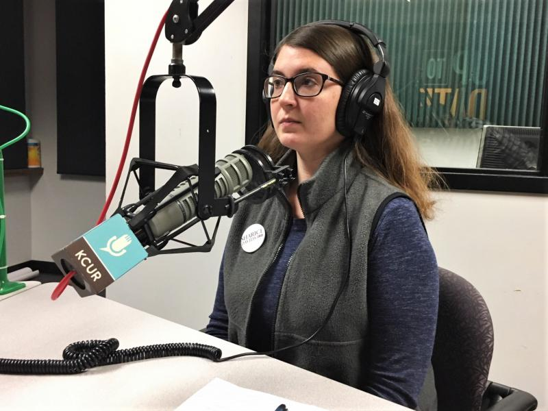 Young white woman with long brunette hair and wearing glasses sits in front of a microphone with headphones on in the KCUR studio.