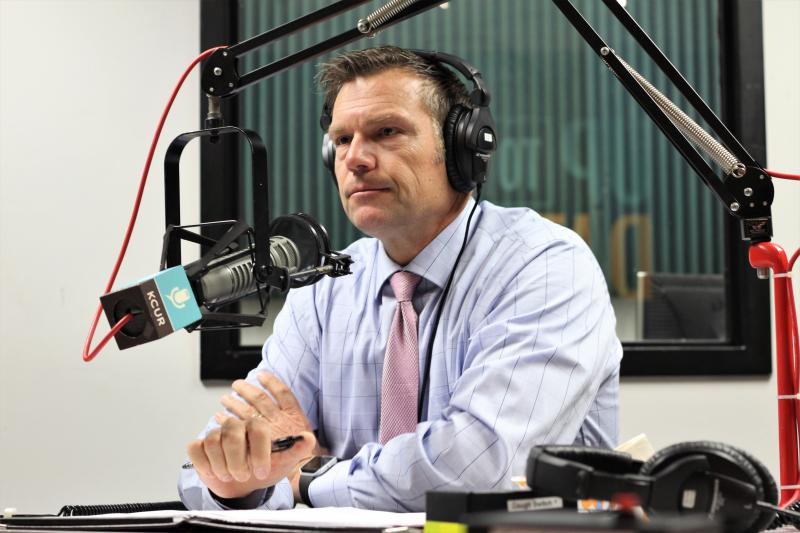 Kris Kobach dressed in a blue dress shirt and tie sits at a microphone.