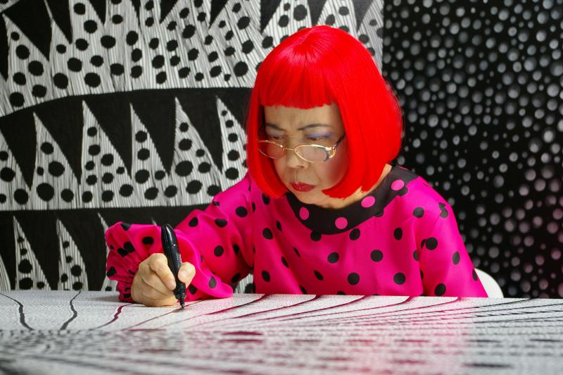 An artist in a bright red wig and pink and black polka dotted blouse draws in her studio.