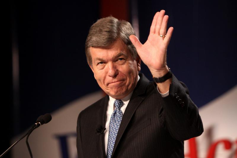 A man in a black suit and blue tie waved to an unpictured crowd after having just given a speech.