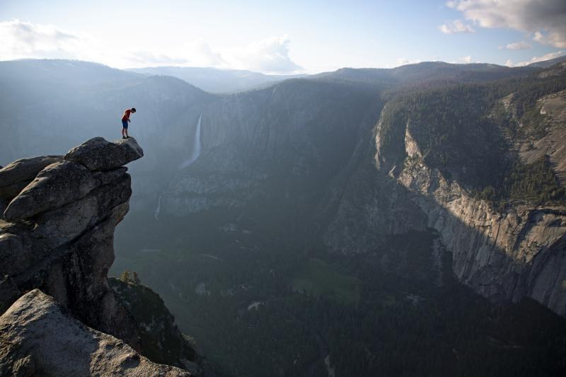 A man stands at the edge of a cliff, looking down.