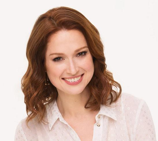 A smiling person with shoulder-length red hair. Wearing a white shirt and positioned in front of a light neutral background.