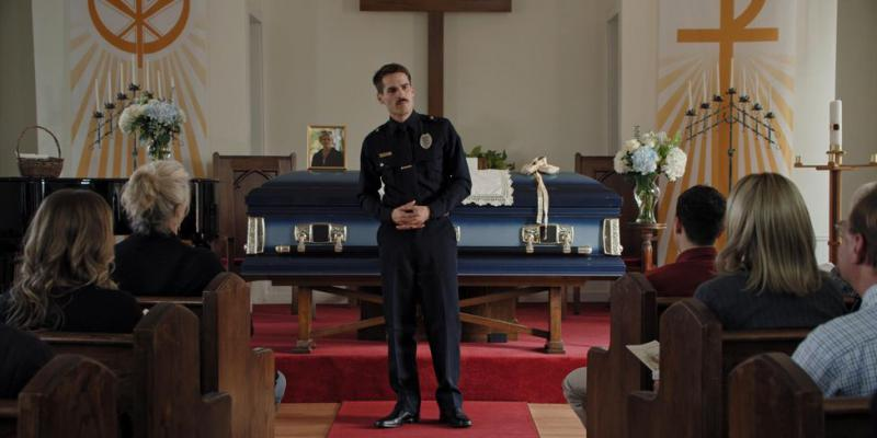 A police officer stands in front of a casket at his mother's funeral.