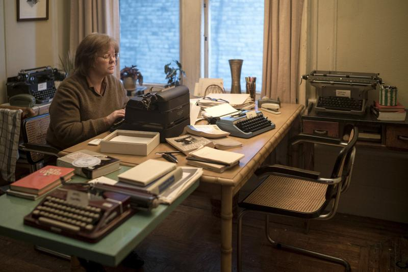 A middle aged woman sits at a cluttered desk typing on a type writer.